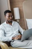 Fotografie african american businessman using laptop in hotel room