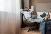 usmívající se mladý americký podnikatel relaxační v hotelovém pokoji s notebookem
