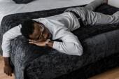 vyčerpání afroamerické muže v oblasti formálního oblečení, spí na posteli v hotelovém pokoji