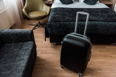black suitcase for travel in hotel room with bed and armchair