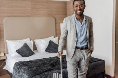 handsome smiling african american businessman with suitcase in hotel room
