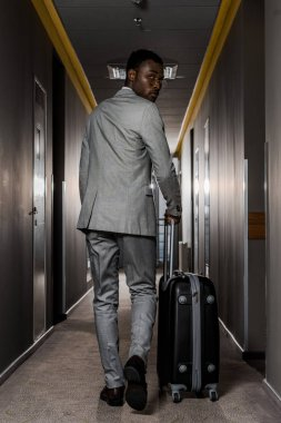 back view of african american businessman with baggage walking in hotel corridor