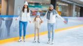 šťastná rodina drží za ruce a společně Bruslení na kluzišti