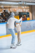 Fotografie father and daughter in knitted sweaters skating on ice rink together