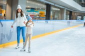 Fotografie smiling mother and daughter holding hands and skating on ice rink together