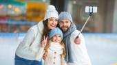 Ať se usmívám rodinné pořizování selfie na smartphone na kluziště