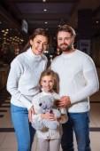 portrét rádi, rodiče a dcera s plyšovým medvědem při pohledu na fotoaparát