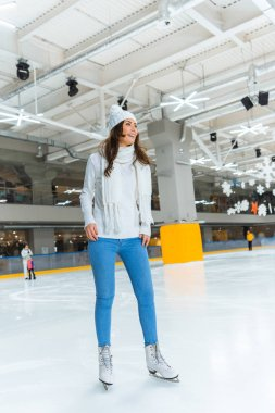 Cheerful young woman in white sweater skating on rink alone stock vector