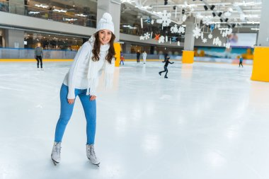 Smiling young attractive woman in knitted sweater skating on ice rink alone stock vector