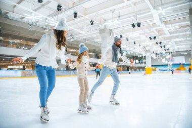 smiling family holding hands while skating together on ice rink