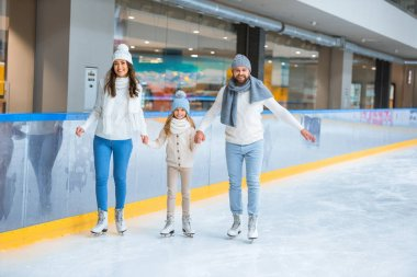 Happy family holding hands while skating together on ice rink stock vector