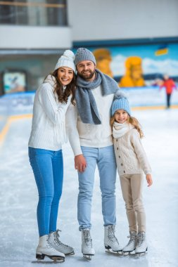 Smiling parents and daughter in sweaters looking at camera on skating rink stock vector