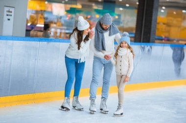 Smiling parents looking at daughter while skating on rink together stock vector