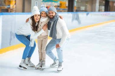 cheerful parents and daughter in sweaters looking at camera on skating rink