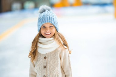 Portrait of happy kid in knitted hat looking at camera on skating rink stock vector