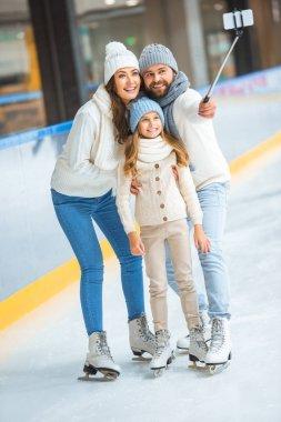 Smiling family taking selfie on smartphone on skating rink stock vector