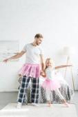 Šťastný otec a roztomilá malá dcera v růžové tutu sukně, drželi se za ruce a tančí doma