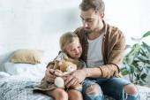 padre guardando la piccola figlia sveglia che si siede con orsacchiotto sul letto