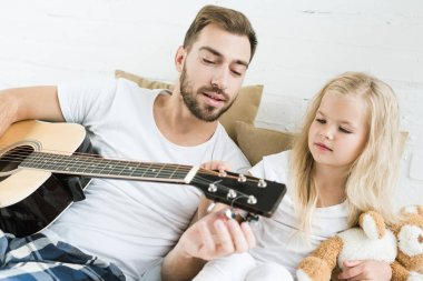 father and cute little daughter playing acoustic guitar together on bed