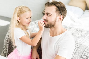 cute little daughter applying red lipstick to happy bearded father at home