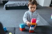 Fényképek elsősorban a színes műanyag blokkok otthon játszó kisfiú