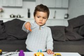 Fotografie child playing with toy airplane in living room at home