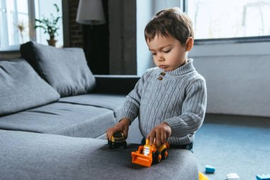 cute boy playing with toy cars in living room at home