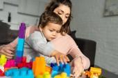 piccolo ragazzo e sua madre che gioca con i blocchi di plastica variopinti a casa