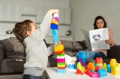 selective focus of little boy playing with colorful plastic blocks while his mother sitting behind at home