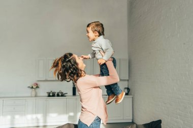 side view of smiling woman raising up adorable son in living room at home