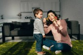 Photo attractive mother showing toy dinosaurs to her little son in living room at home