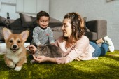 attractive woman and little boy laying on floor with dog and cat in living room at home