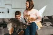 Mutter und Sohn auf Sofa mit Hund und Katze im heimischen Wohnzimmer