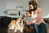 Fotografie glückliche Mutter und Sohn sitzen auf Sofa mit Welsh Corgi Hunde zu Hause