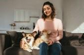 Fotografie atraktivní žena sedí na pohovce s welsh corgi psy doma