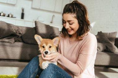 attractive smiling woman petting cute welsh corgi pembroke at home