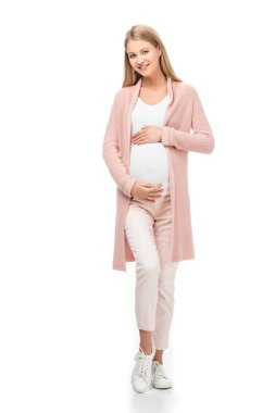 Full length of pregnant woman in pink cardigan touching belly isolated on white stock vector