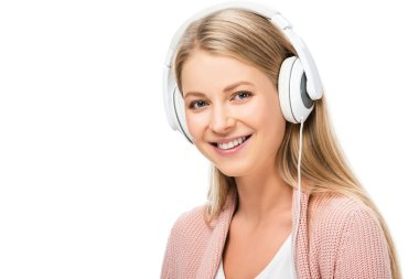 smiling woman listening music, using headphones and looking at camera isolated on white