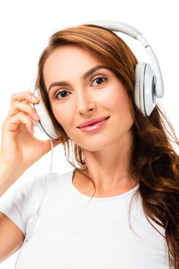closeup of woman looking at camera, listening music and using headphones isolated on white