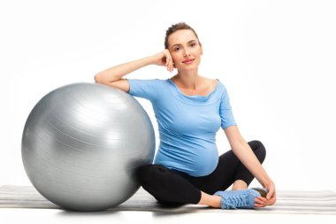 pretty brown haired pregnant woman sitting on floor with fitness ball isolated on white