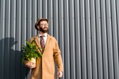 Fotografie smiling happy man in hat and glasses holding plant in bright pot