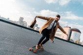 excited businessman riding on penny board with bag in hand