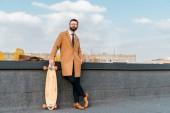 vousatý podnikatel v brýlích s penny board na střeše