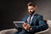 vážný podnikatel pomocí digitálních tabletu a sedí v křesle