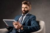 Jistý podnikatel drží digitální tabletu a sedí v křesle
