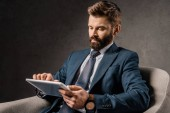 bearded businessman using digital device while sitting in armchair