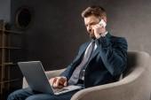 selbstbewusster Geschäftsmann, der im Sessel sitzt und Gadgets benutzt
