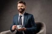 usmíval se podnikatel sedí v křesle s šálkem kávy