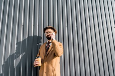 low angle view of businessman talking on smartphone and holding coffee to go