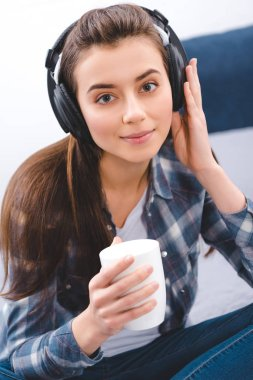 beautiful young woman in headphones holding cup and smiling at camera
